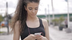 Beautiful fitness model, setting a stopwatch on her smartphone, run away Stock Footage