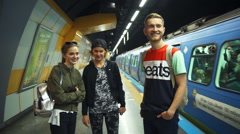Three young people and the moving train on subway platform slow motion Stock Footage