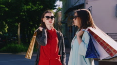Two women enthusiastically talk about their purchases. In the hands holding Stock Footage