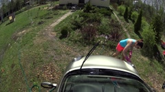 Playful girl washing car on sunlight at Vacation home on green grass Stock Footage