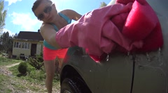Girl washing car on water splashing with pink sponge and sunlight, Low angle - stock footage