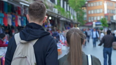 Back view of a couple walking in the street slow motion Stock Footage