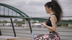 Curly fitness model, sitting on the bench, playing music on smartphone Stock Footage