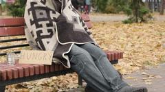 Hungry homeless frozen man sitting on bench and trying to get warm, poverty Stock Footage