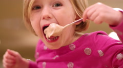 Messy young girl eats ice cream and her mom wipes off her face Stock Footage