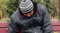 Homeless drunk sleeping on bench in park, unhappy life of poor addicted man Stock Footage