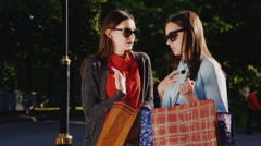 Two young women after a successful shopping experience. They show each other - stock footage