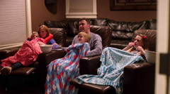 A family watching a movie in a home theater with blankets and popcorn Stock Footage