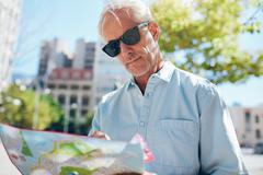 Mature tourist consulting a map while touring a foreign city - stock photo
