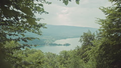 Peaking through leafs to view a big lake with mountains and a small castle Stock Footage