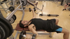 Yong man train with weights at the gym Stock Footage
