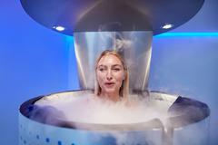 Woman in a whole body cryotherapy cabin Stock Photos