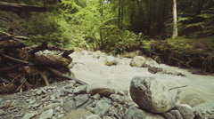 Turbid water flowing rapidly towards the camera in a creek with some rocks Stock Footage