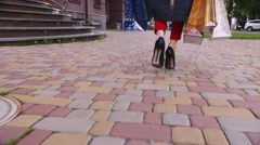 Woman with shopping bags walking on the sidewalk, in the frame are only visible - stock footage
