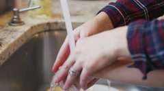 A mother helping her daughter wash her hands in the kitchen sink Stock Footage