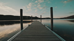 Symetric shot of an old wooden dock on a clear lake with small hills Stock Footage