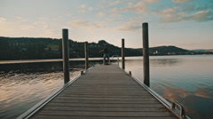 A kid fishing at the end of an old wooden dock on a crystal clear lake Stock Footage