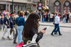 Woman is taking pictures on the street of Bruges - stock photo
