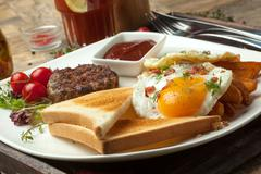 Minced beef on the grill with  fried eggs, crisp and toast. - stock photo
