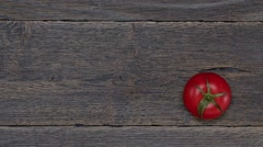 Red tomatoes on the wooden background stop motion - stock footage