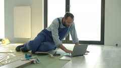 Male worker working with laptop and during renovation at new home Stock Footage