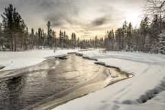 Snow-covered riverbank under the sunset sky. Northern Karelia. Russia. - stock photo
