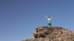 Tourist with turban and sunglasses spreading arms on big rock in desert, Egypt. Stock Footage