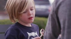 A little girl eating a cake pop and holding it up Stock Footage