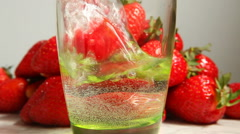 Strawberry falling into glass in water with splash, strawberries on background Stock Footage