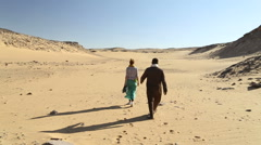 Nubian man walking with female tourist in desert Stock Footage