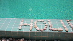 The inscription holiday is laid out by pebble on a pool side - stock footage