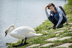 Young woman posing with white swan on the lakeside Stock Photos