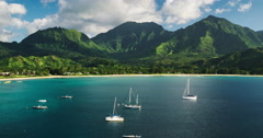 Aerial view flying over sail boats in Hanalei Bay towards beautiful green mou Stock Footage