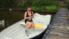 Girl sitting in a boat texting and looking for replay Stock Footage