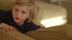 A little girl plays on the couch while her mom wipes food from her face Stock Footage