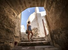 Girl under a arc in an old village . Stock Photos
