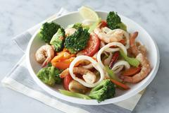 Plate of prawns, squid and vegetables Stock Photos