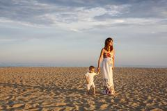 Mother and toddler walking along beach, holding hands Stock Photos