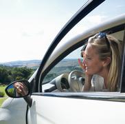 Mature woman applying make up in mirror of car Kuvituskuvat