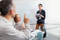 Businesswoman presenting to colleagues - stock photo