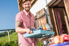 Young man carrying tray outside chalet, Tyrol, Austria - stock photo