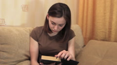 Girl reading book on sofa Stock Footage