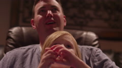 A young girl watching a movie on her dad's lap in a home theater Stock Footage