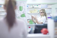 Pharmacist looking at box of medication Stock Photos