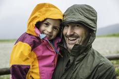 Father and daughter in rainproof jackets - stock photo