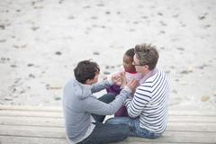 Gay couple and child at beach Stock Photos