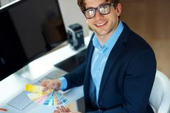 Man looking to a color paint palette at home office - stock photo