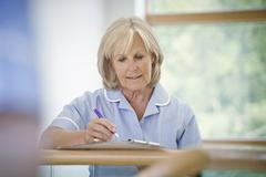 Mature female nurse in hospital corridor with clipboard Stock Photos