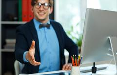 Modern business man with arm extended to handshake Stock Photos