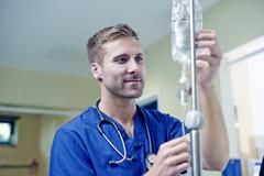 Doctor checking intravenous drip in hospital - stock photo